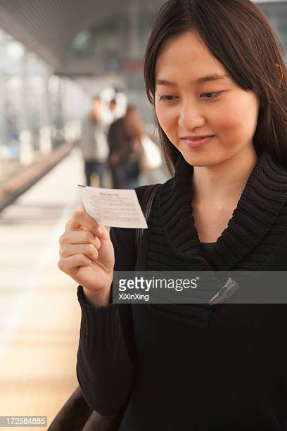 Young Woman Looking At Train Ticket on Railroad Platform