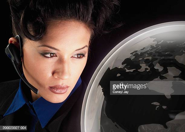 Young woman looking at transparent globe (Digital Composite)