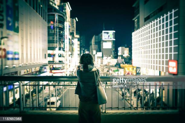 young woman looking at urban city view at night - solitude stock pictures, royalty-free photos & images