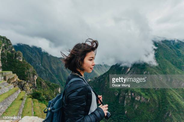 young woman looking at view from machu picchu in peru - travel stock pictures, royalty-free photos & images
