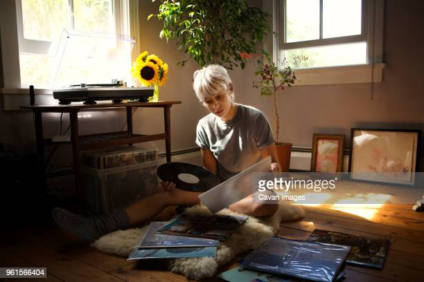 young woman looking at vinyl records while sitting on floor at home - collection photos et images de collection