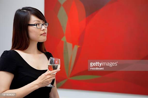 Young woman looking at wall paintings in art gallery