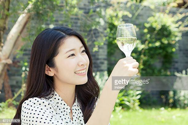 Young woman looking at wine glass