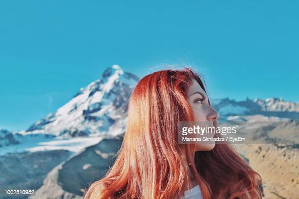 Young Woman Looking Away Against Mountains In Winter