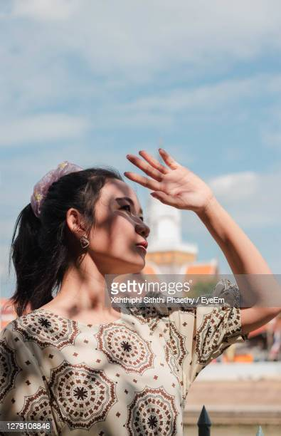 young woman looking away against sky - models in stockings stock pictures, royalty-free photos & images
