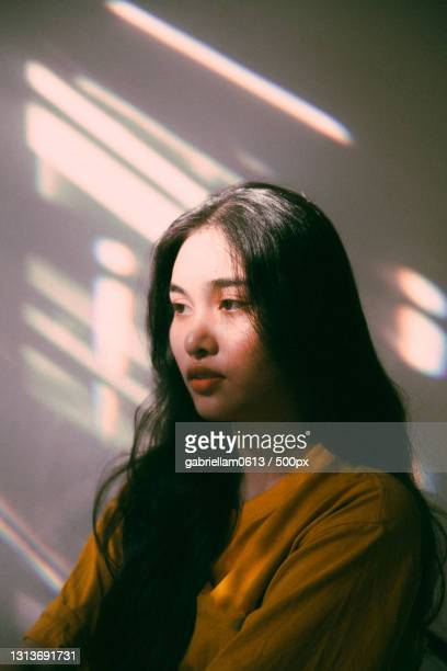 young woman looking away against wall - editorial stock pictures, royalty-free photos & images
