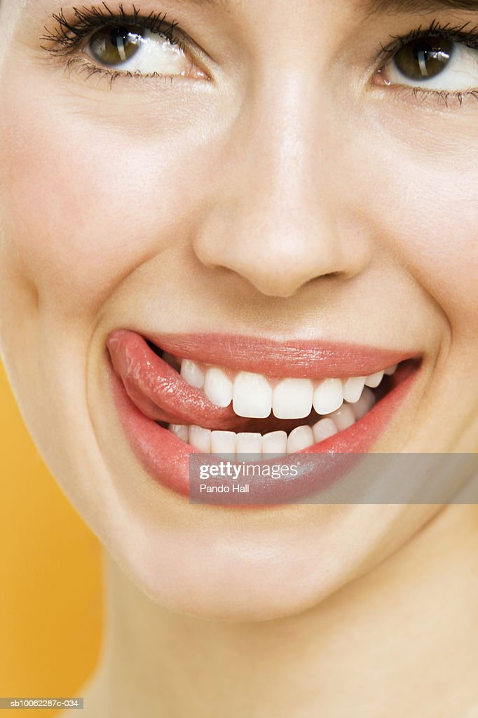 Young woman looking away and smiling, licking lips, close-up : Stock Photo