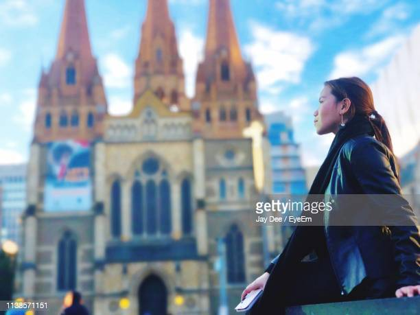 young woman looking away by cathedral in city - catholicism stock pictures, royalty-free photos & images