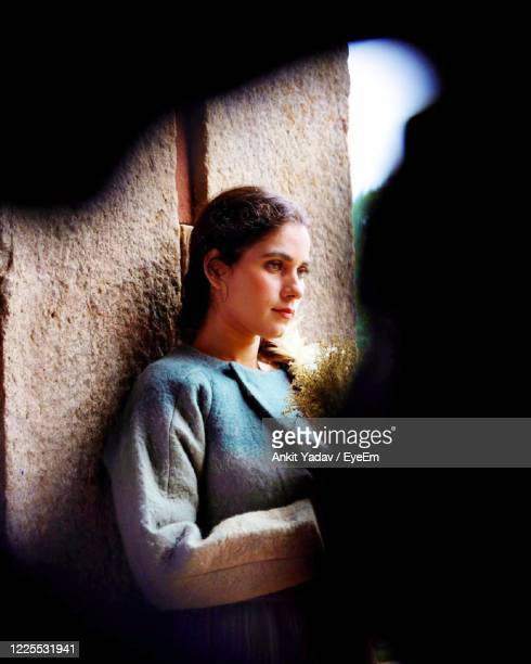 young woman looking away seen through hole - prayagraj stock pictures, royalty-free photos & images