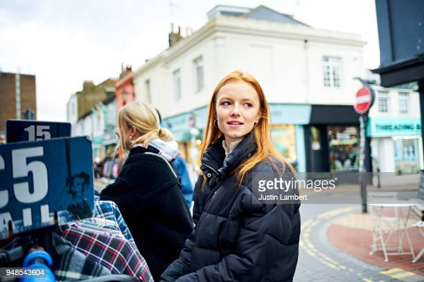 Young woman looking away while shopping for vintage clothes outside a second hand clothing store