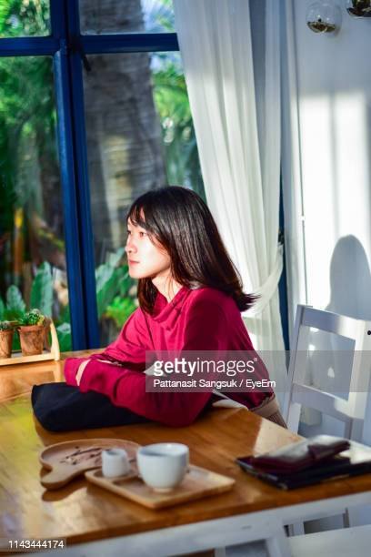young woman looking away while sitting at table - pattanasit stock pictures, royalty-free photos & images