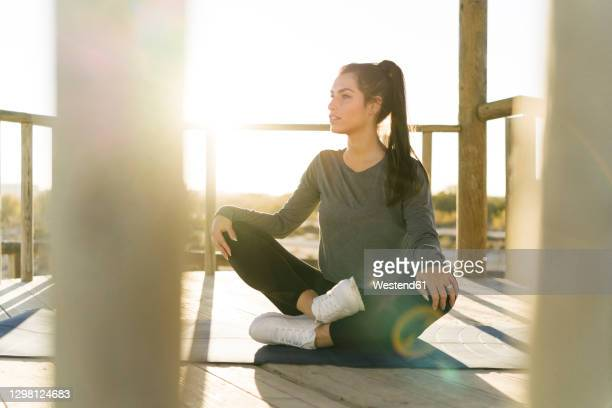 young woman looking away while sitting on exercise mat in gazebo at sunset - manches longues photos et images de collection