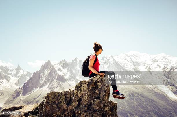 young woman looking away while sitting on rock against sky - haute savoie fotografías e imágenes de stock