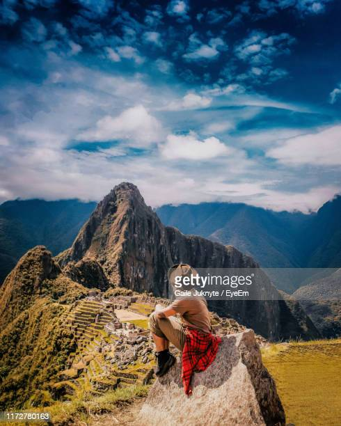 young woman looking away while sitting on rock - マチュピチュ ストックフォトと画像