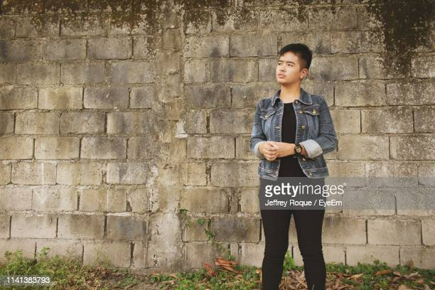 young woman looking away while standing against wall - jeffrey roque stock photos and pictures