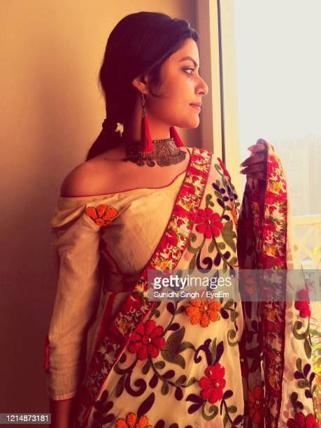 young woman looking away while standing against wall - sari stock pictures, royalty-free photos & images