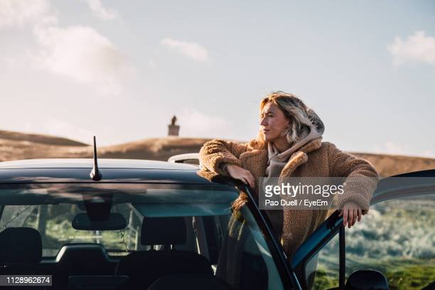 young woman looking away while standing by car against sky - dänemark stock-fotos und bilder