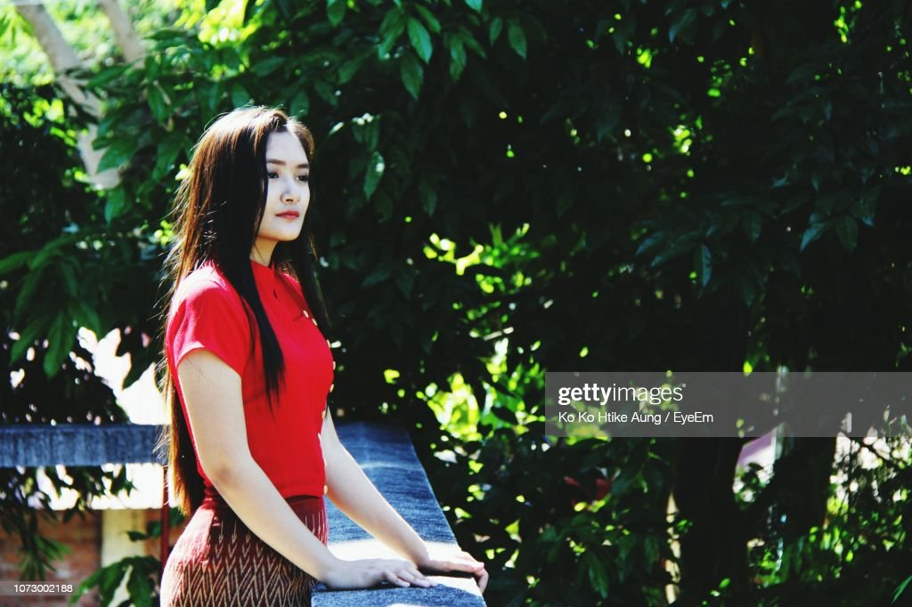 Young Woman Looking Away While Standing By Railing : Stock Photo