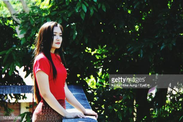 young woman looking away while standing by railing - ko ko htike aung stock pictures, royalty-free photos & images