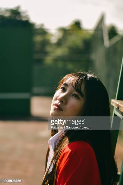 young woman looking away while standing outdoors - pattanasit stock pictures, royalty-free photos & images