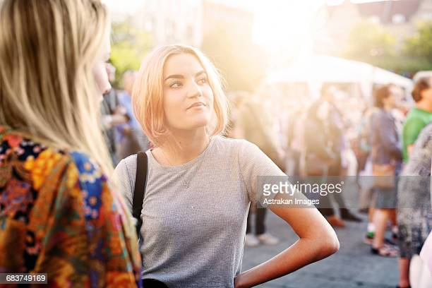 Young woman looking away while standing with friend at music festival
