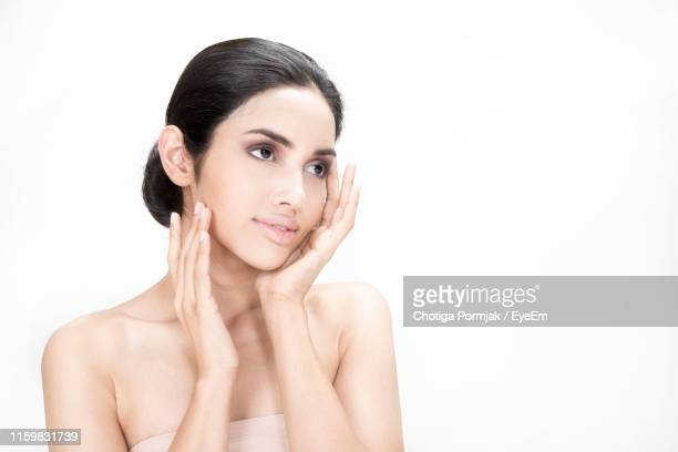 young woman looking away while touching cheeks against white background - cheek stock pictures, royalty-free photos & images