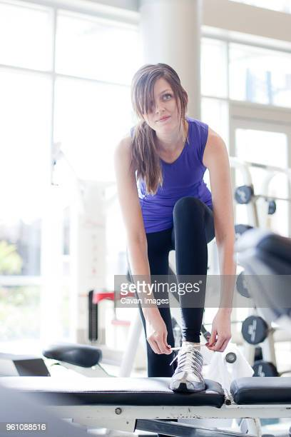 young woman looking away while tying shoelace in gym - lace fastener stock pictures, royalty-free photos & images