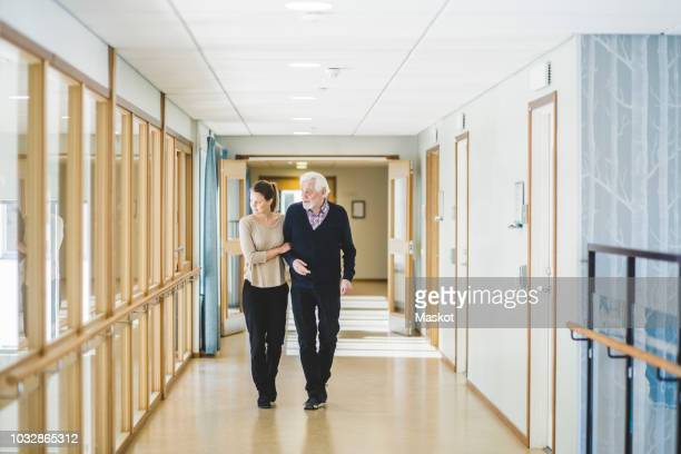 young woman looking away while walking with grandfather in corridor at nursing home - retirement community stock pictures, royalty-free photos & images