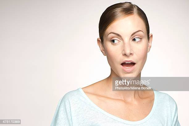 Young woman looking away with mouth open in surprise, portrait