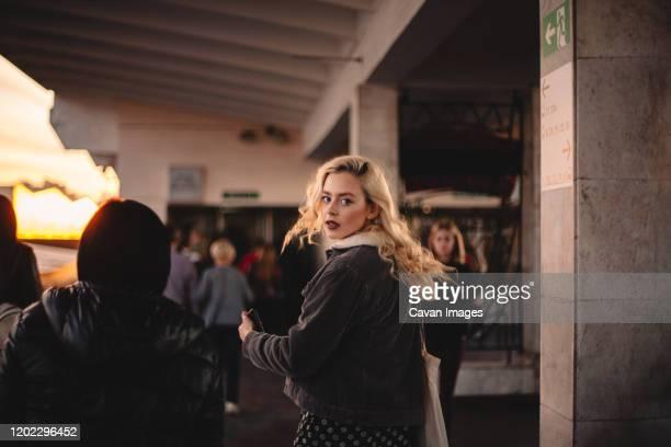 young woman looking back at camera walking on subway station - woman hurry stockfoto's en -beelden