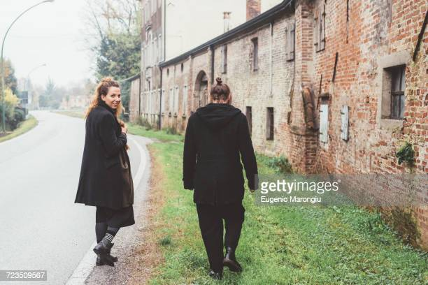 Young woman looking back while strolling with boyfriend on rural road