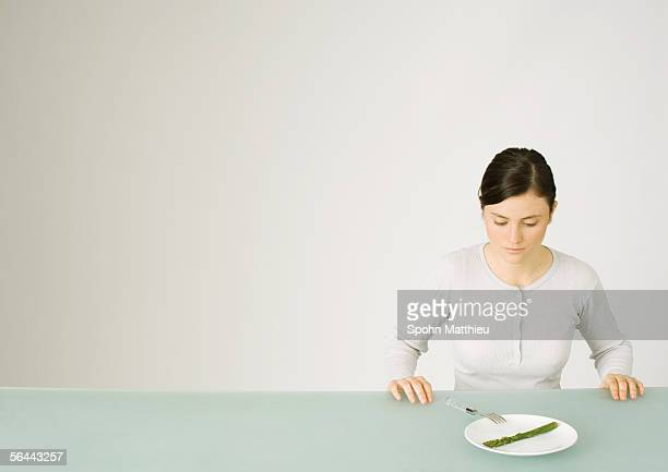 Young woman looking down at single asparagus on plate
