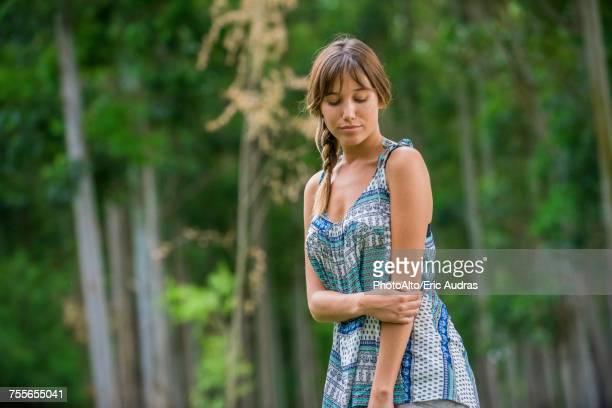 young woman looking down outdoors - down blouse stockfoto's en -beelden