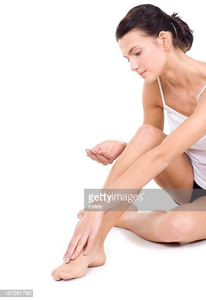 Young woman looking down putting moisturizer on leg