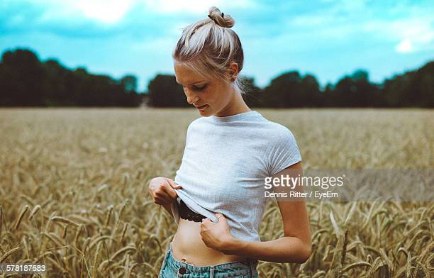 Young Woman Looking Down While Holding T-Shirt On Field