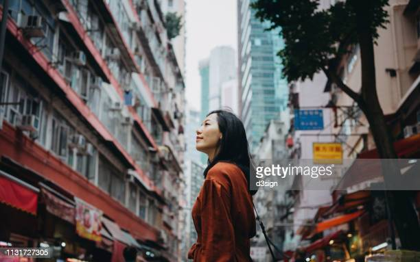 young woman looking far away in city with local street scene in hong kong - explore stock photos and pictures