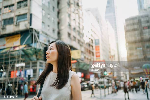 young woman looking far away in city with local street scene in hong kong - 迷う ストックフォトと画像