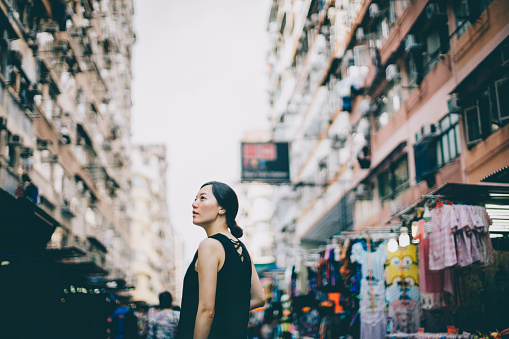 Young woman looking far away in city with local street scene in Hong Kong - gettyimageskorea