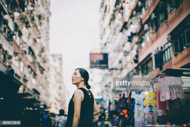 Young woman looking far away in city with local street scene in Hong Kong