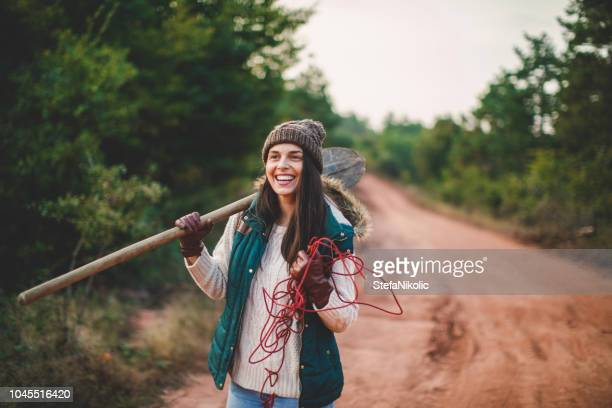 young woman looking for a christmas tree in the forest - tree farm stock pictures, royalty-free photos & images