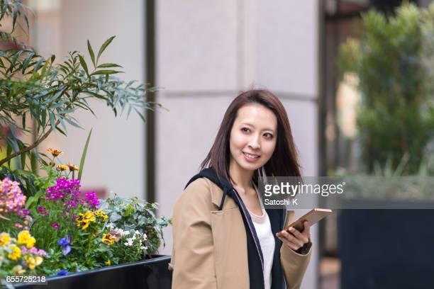 スマート フォンを使用して場所を探している若い女性 - 待つ ストックフォトと画像