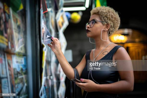 young woman looking for the news at newsstand - news stand stock pictures, royalty-free photos & images