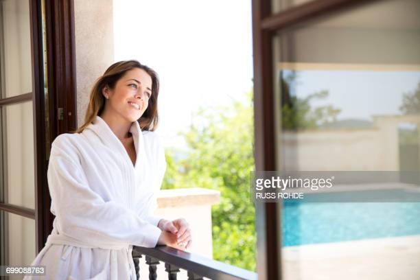 young woman looking from window of boutique hotel suite, majorca, spain - guest stock pictures, royalty-free photos & images