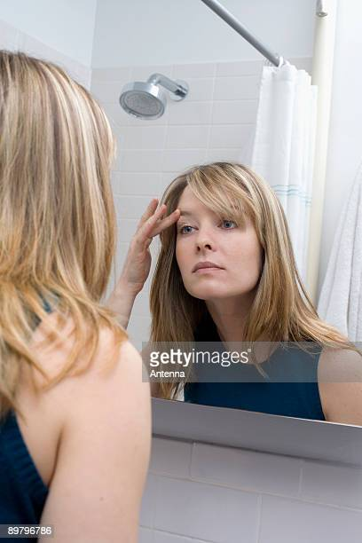 A young woman looking in a bathroom mirror