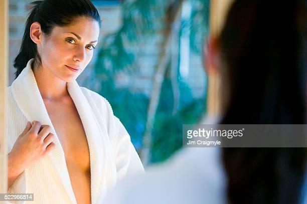 young woman looking in a mirror - decote peito imagens e fotografias de stock
