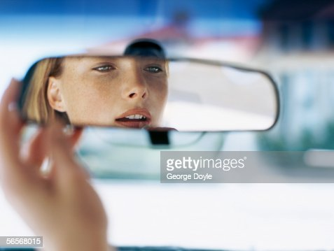 Young Woman Looking In A Rear View Mirror In A Car High ...
