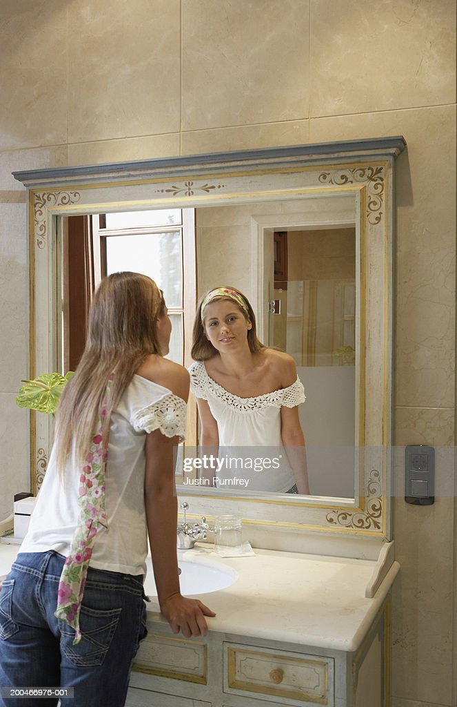 Young Woman Looking In Bathroom Mirror Leaning On Sink