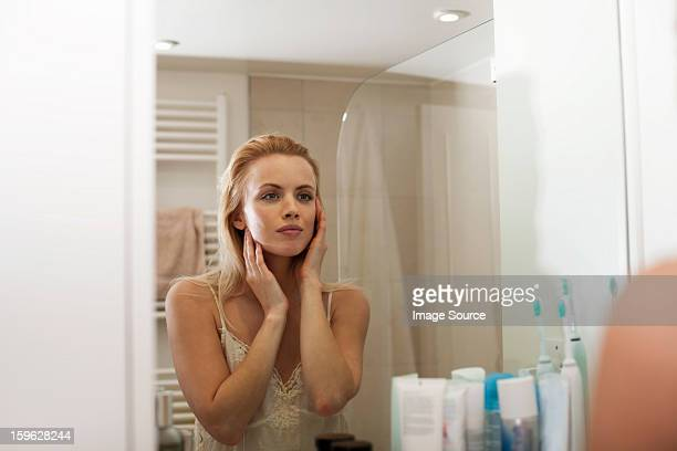young woman looking in bathroom mirror - vanity stock pictures, royalty-free photos & images