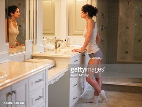 Young Woman Looking In Bathroom Mirror Side View Stock