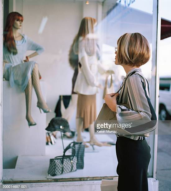 Young woman looking in clothes shop window